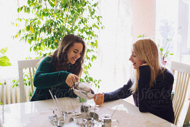 Two female friends drinking tea and talking by Jovana Rikalo for Stocksy United