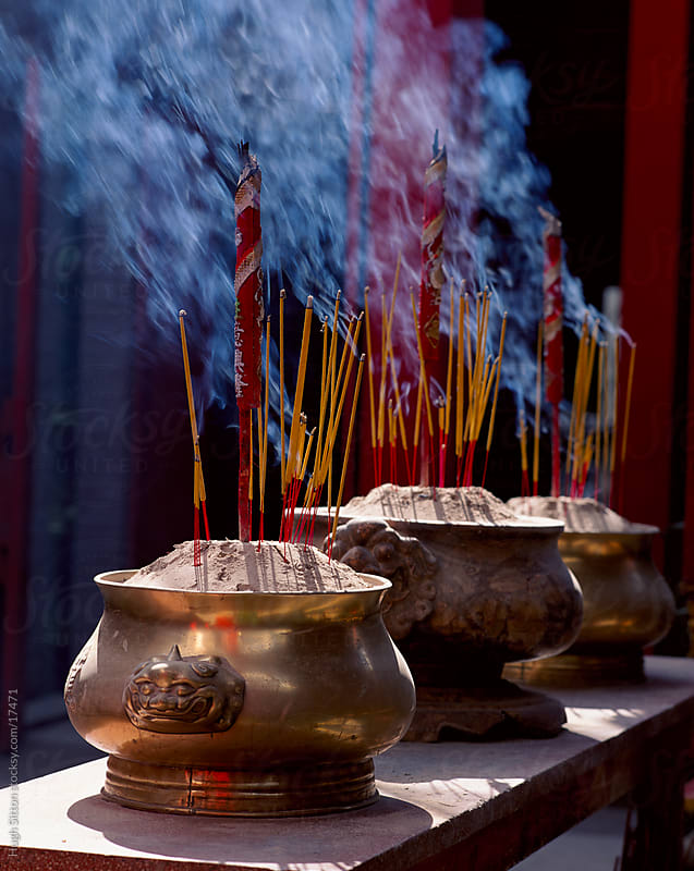Incense sticks burning inside temple.  by Hugh Sitton for Stocksy United