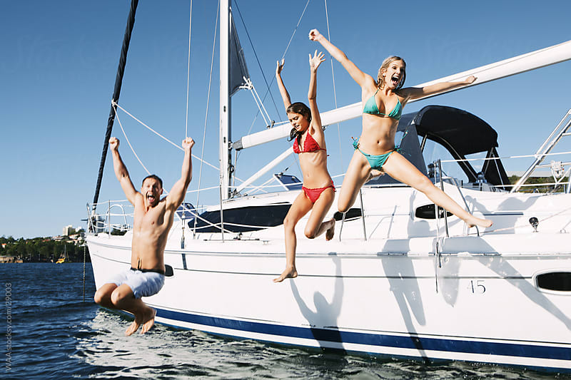 Joyful friends jumping from a yacht by WAA for Stocksy United