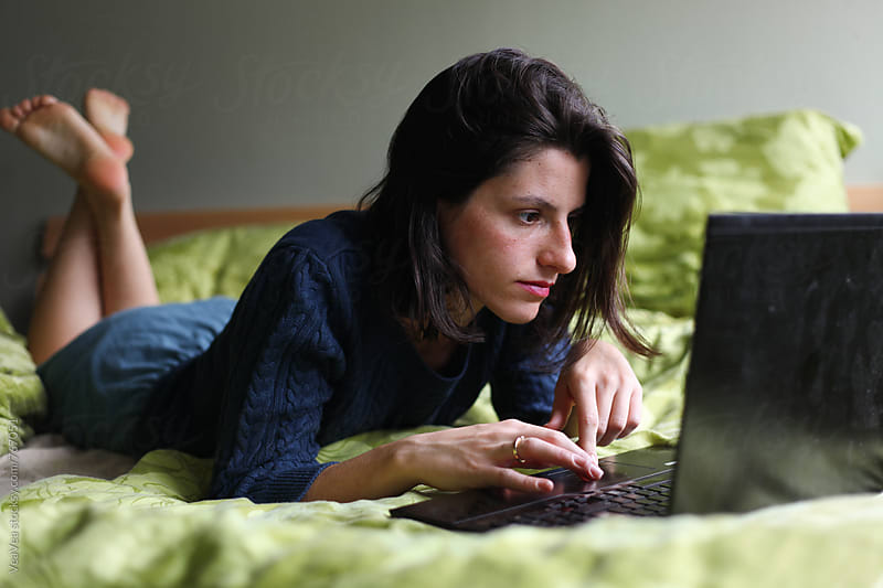 Woman using her laptop on the bed  by Marija Mandic for Stocksy United
