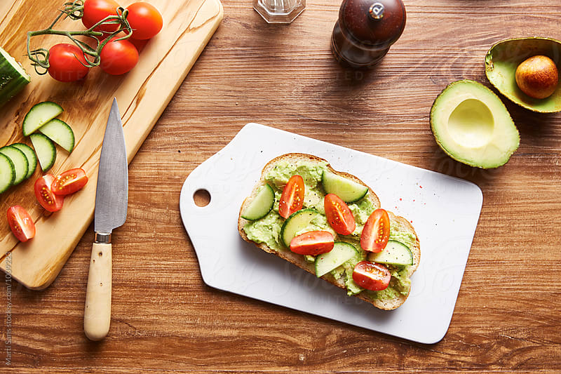 Delicious avocado toast with tomatoes and cucumber by Martí Sans for Stocksy United