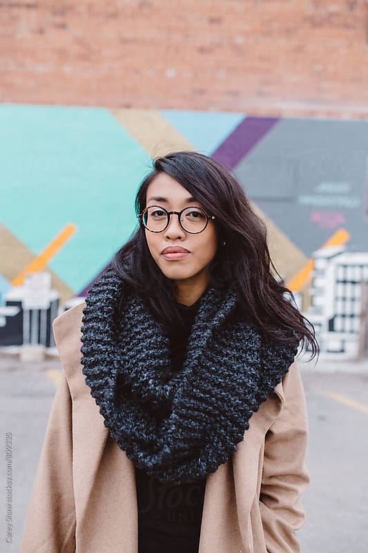 Portrait of urban woman wearing large knit scarf by Carey Shaw for Stocksy United