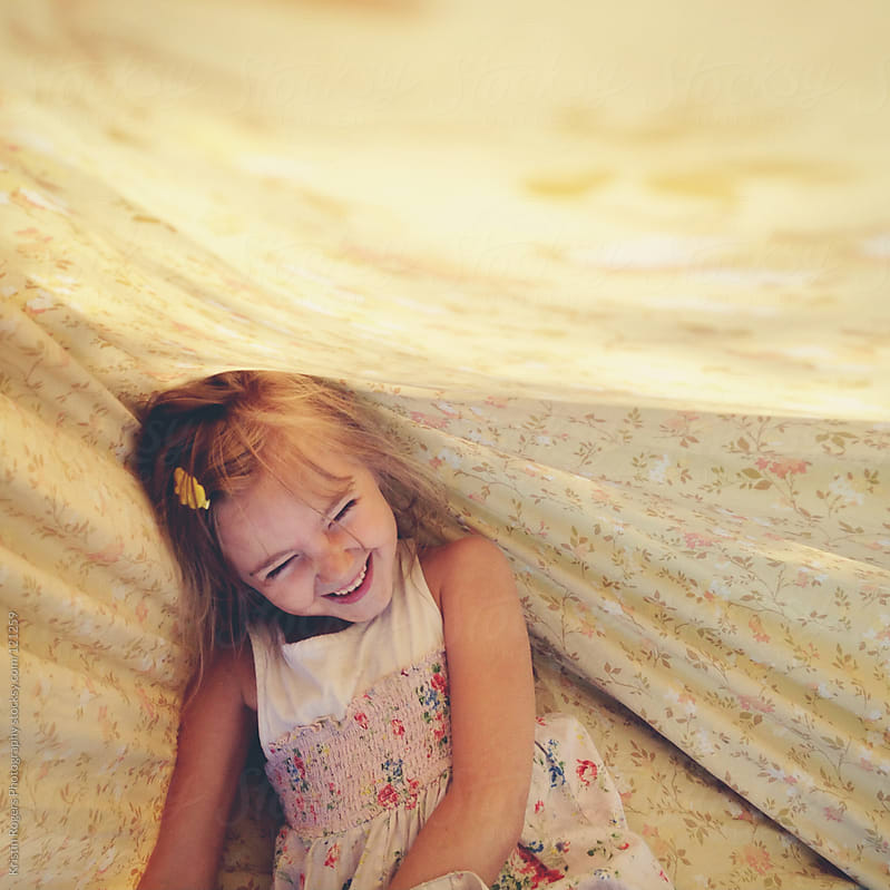 young girl laughing while playing in sheets by Kristin Rogers Photography for Stocksy United