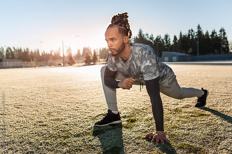African American athlete stretching on the football field by Suprijono Suharjoto for Stocksy United