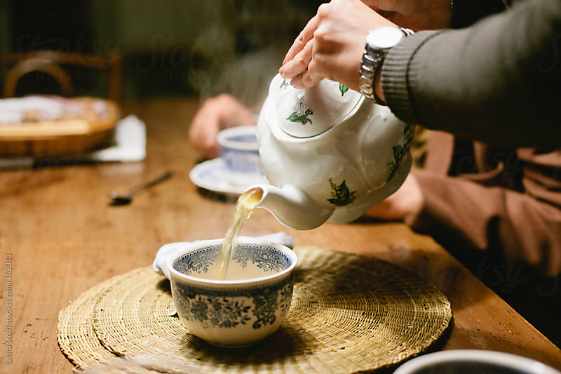 Drinking tea all together  by Laura Stolfi for Stocksy United