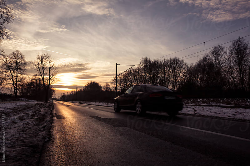 Car on country road into the sunrise by Mima Foto for Stocksy United