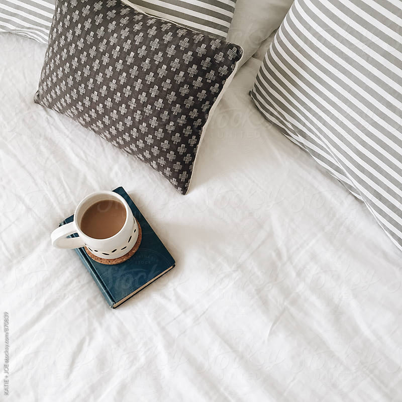 Mug of coffee or tea sitting on a book on a white bed with striped pillows by KATIE + JOE for Stocksy United