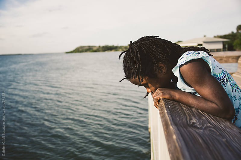 Black girl leaning over a boardwalk by Gabriel (Gabi) Bucataru for Stocksy United