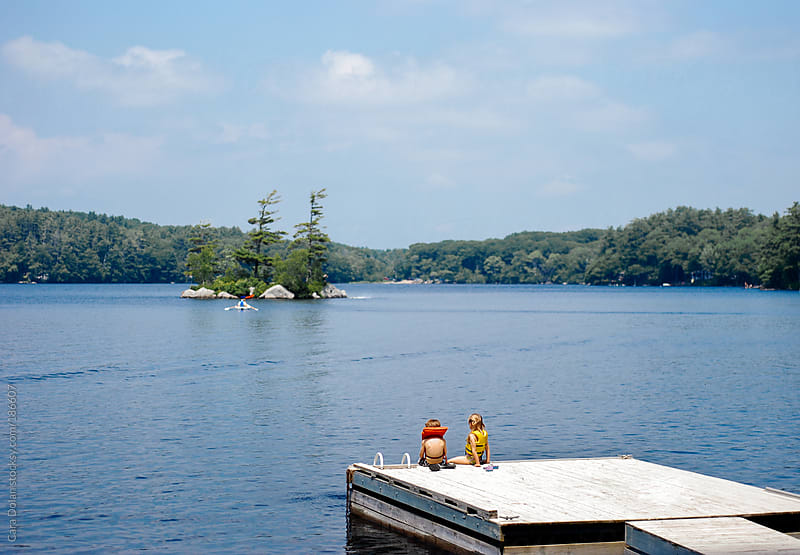 Kids sit on a dock on a lake in summer by Cara Dolan for Stocksy United