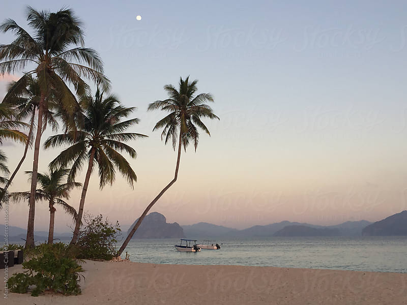 beach with evening light and the moon in the sky by Marta Muñoz-Calero Calderon for Stocksy United