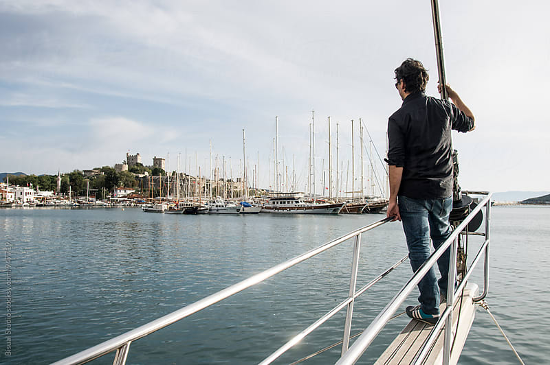 Young man on a sailing boat gazing at the Bodrum's castle in Bodrum, Turkey by Bisual Studio for Stocksy United