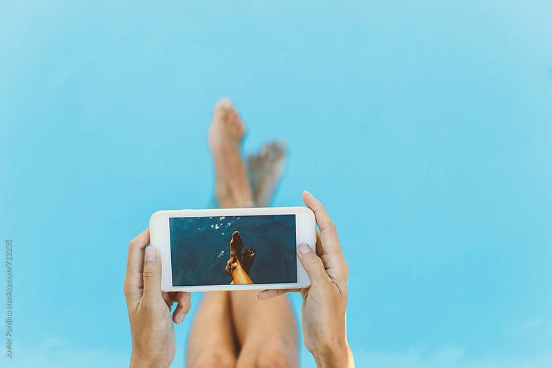using phone on the pool by Javier Pardina for Stocksy United