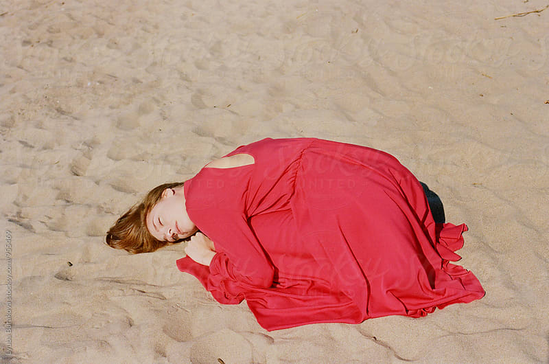 Young woman wearing red dress lying on a sand by Lyuba Burakova for Stocksy United
