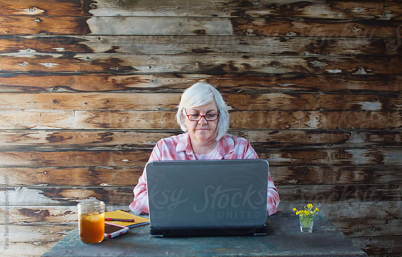 senior woman working at laptop by Tana Teel for Stocksy United