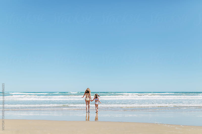 Little Sisters Walking into the Sea  by VICTOR TORRES for Stocksy United