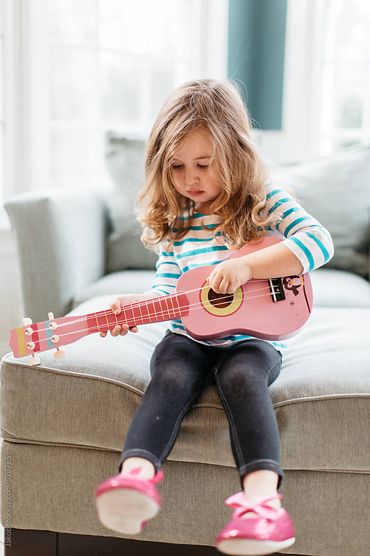 Cute toddler playing a toy guitar by Jakob for Stocksy United