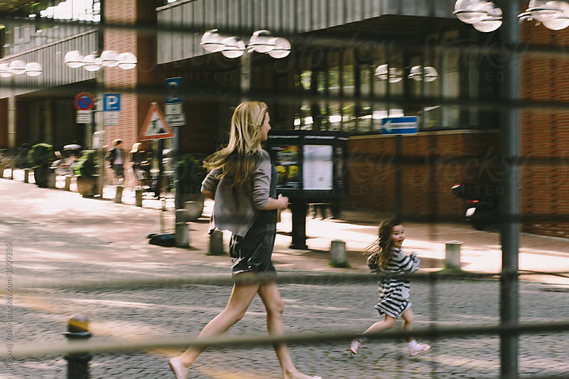 Mother and daughter running along the street by Evgenij Yulkin for Stocksy United