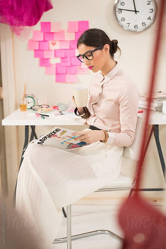 Fashion Designer Reading a Magazine by Lumina for Stocksy United