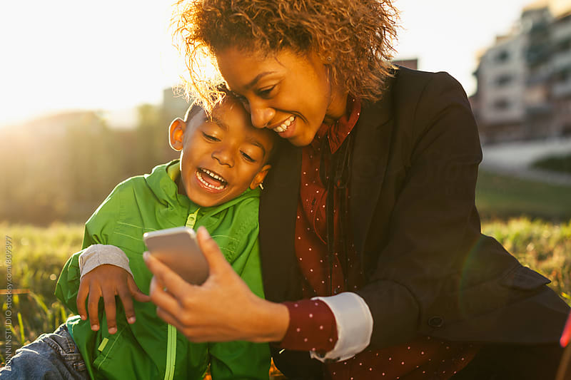 Smiling mother and her son looking smartphone in the park at sunset. by BONNINSTUDIO for Stocksy United