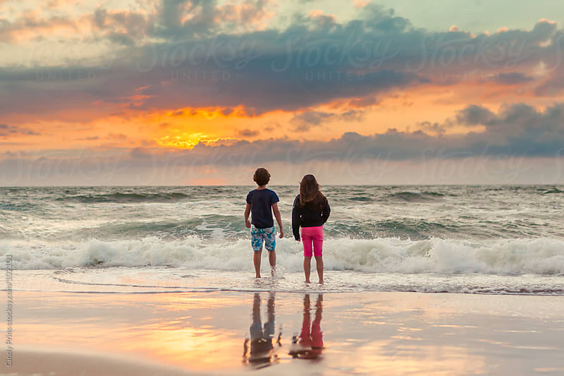 Boy and girl standing in the shoreline watching the sunset by Cindy Prins for Stocksy United