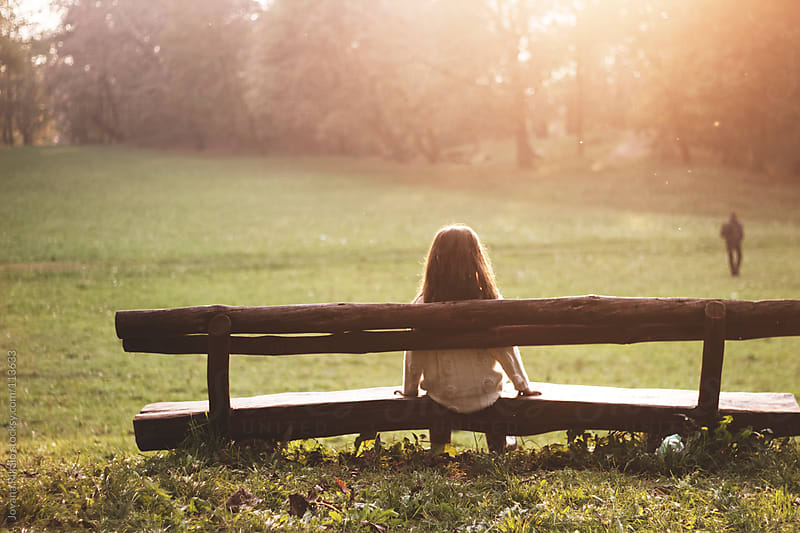 Little girl sitting on bench in the park by Jovana Rikalo for Stocksy United