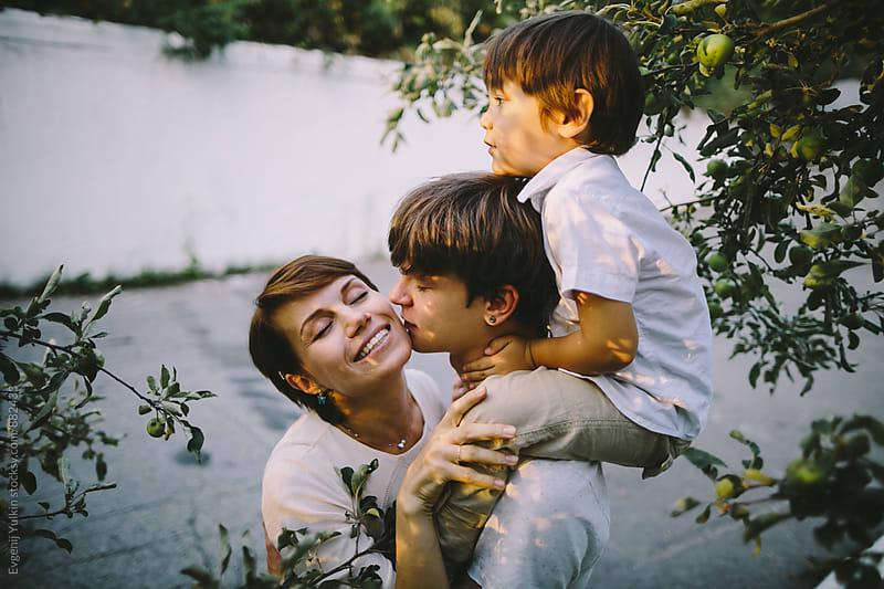 Family under the apple tree by Evgenij Yulkin for Stocksy United