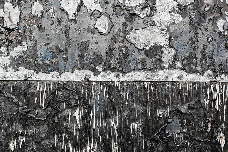 Weathered black paint on a metal and wooden farm door. by Paul Phillips for Stocksy United