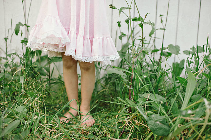 Little girl standing in grass with her pastel pink dress by Kristin Rogers Photography for Stocksy United