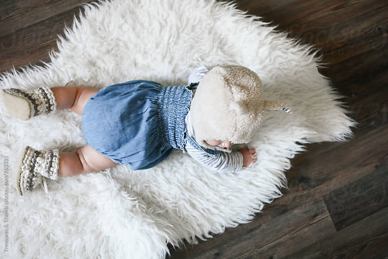 Baby girl laying on sheepskin by Treasures & Travels for Stocksy United