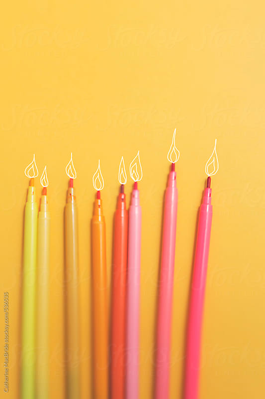 Colourful marker pens with drawn on candle flames.... by Catherine MacBride for Stocksy United