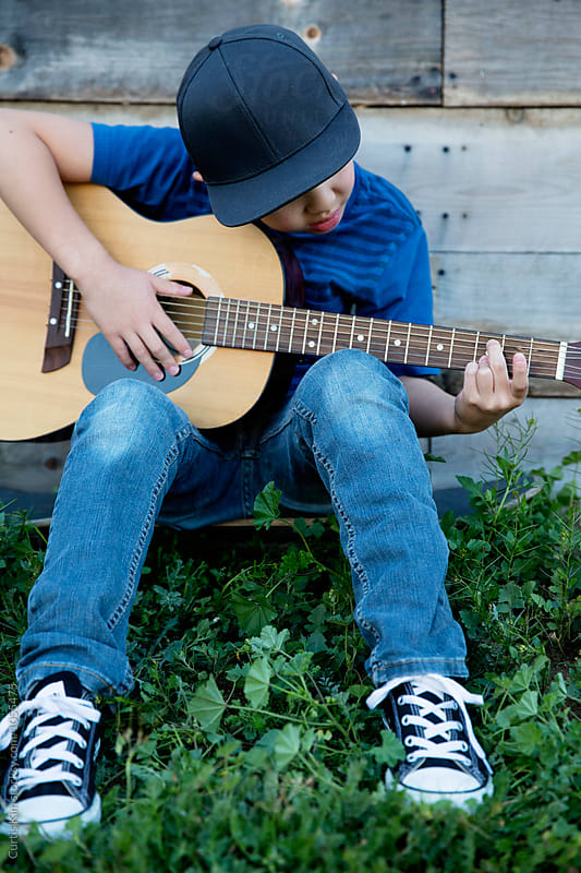 Young boy sitting on skateboard playing guitar by Curtis Kim for Stocksy United