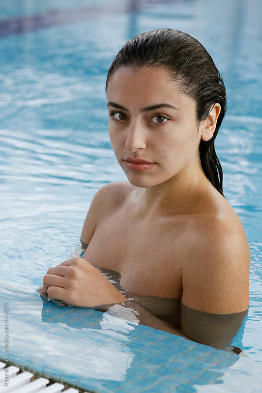 young woman in swimming pool by Rene de Haan for Stocksy United