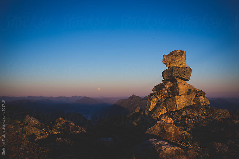 Stacked rocks on a mountain peak at sunset by Christian Tisdale for Stocksy United