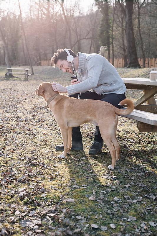 Man in headphones stroking brown dog in park by Alberto Bogo for Stocksy United