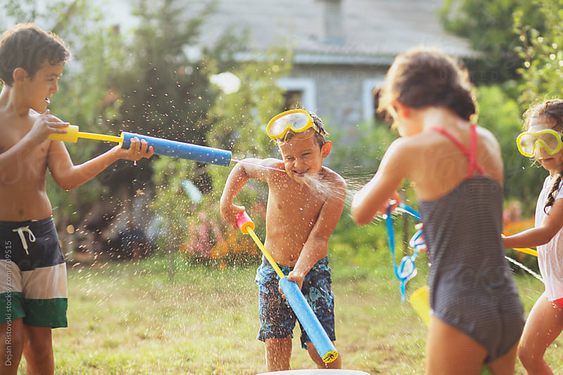 Children playing with water guns in the yard. by Dejan Ristovski for Stocksy United