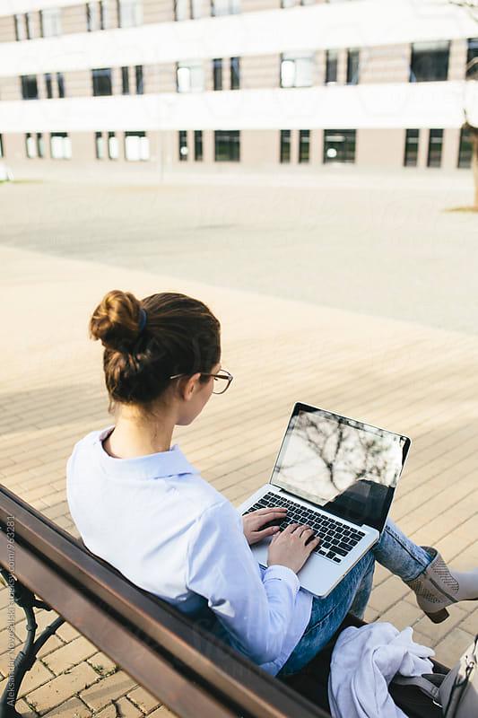 Young businesswoman wworking on laptop, outdoors by Aleksandar Novoselski for Stocksy United