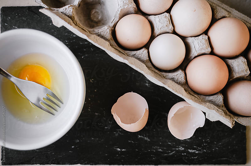 Eggs with cracked eggshell and bowl with yolk by Deirdre Malfatto for Stocksy United