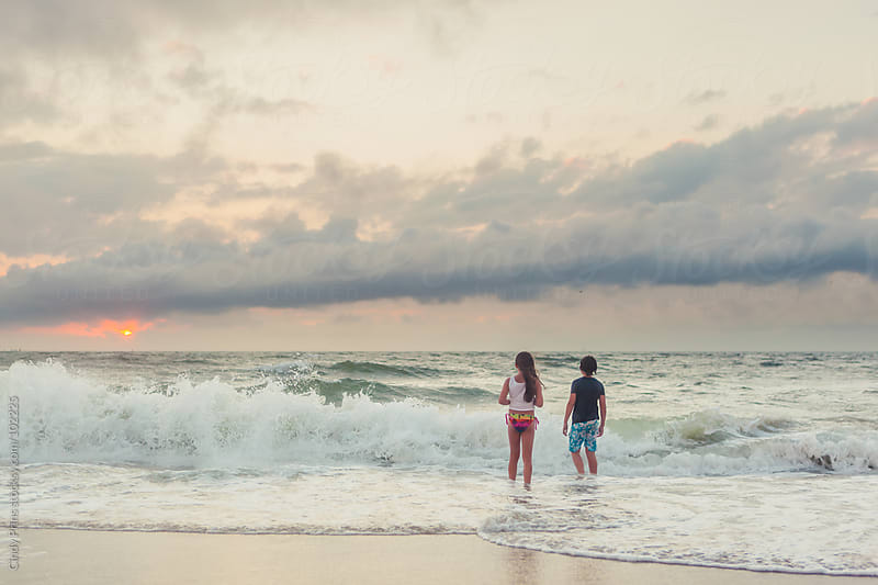 A boy and a girl standing in the ocean watching the sun go down by Cindy Prins for Stocksy United