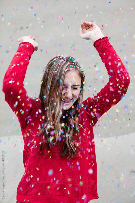 Beautiful teenage girl having fun with confetti by Carolyn Lagattuta for Stocksy United