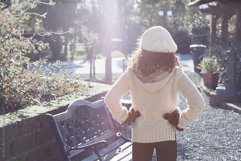 Enjoying Winter Sun: Girl with her hands on waist standing in a park by Beatrix Boros for Stocksy United