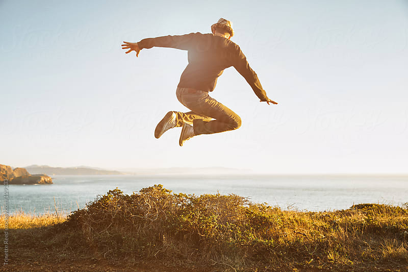 Hipster jumping over bush in nature by Trinette Reed for Stocksy United
