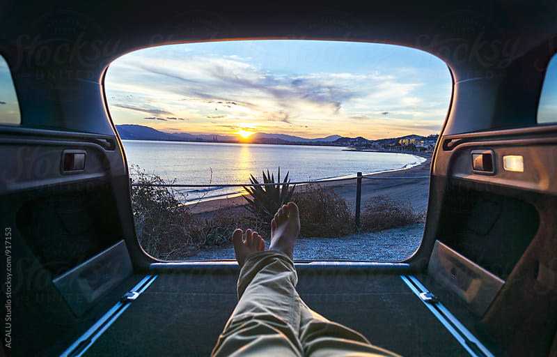 Man in the car looking at beach in the sunset by ACALU Studio for Stocksy United