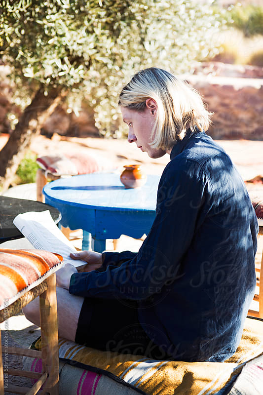 outside reading  by Rachel Schraven for Stocksy United