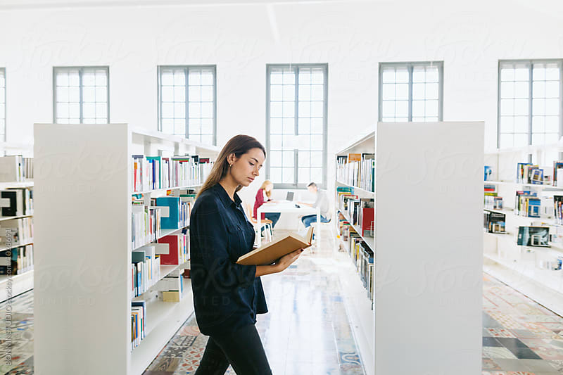 Young university woman reading a book while walking in a library. by BONNINSTUDIO for Stocksy United
