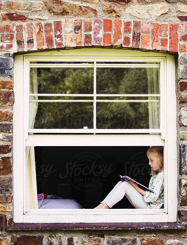 A little girl sitting a window reading a book. by Helen Rushbrook for Stocksy United