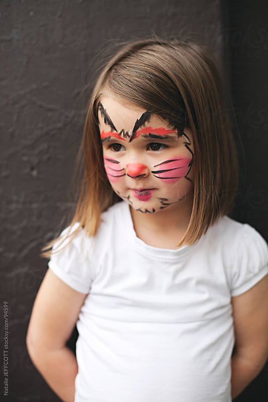 young girl with face painted a s black cat for Halloween by Natalie JEFFCOTT for Stocksy United