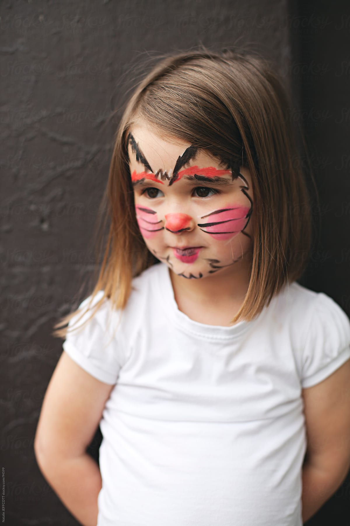 young girl with face painted a s black cat for halloween | stocksy