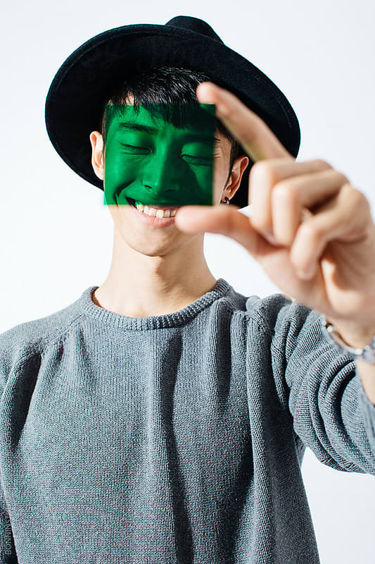Portrait of an asian man smiling holding a green glass. by BONNINSTUDIO for Stocksy United