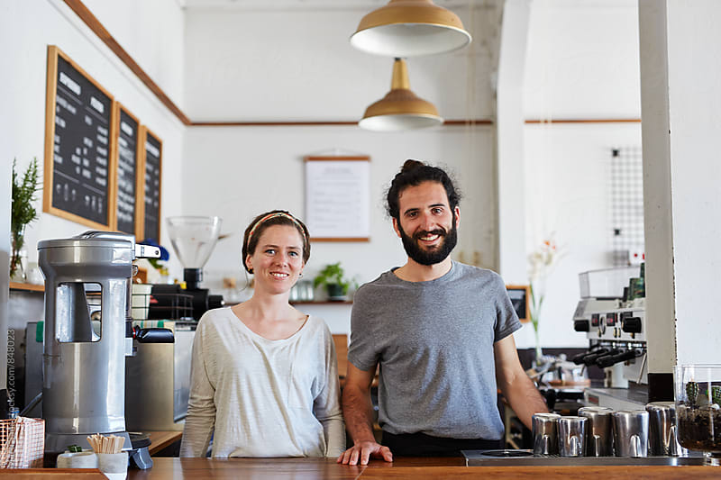 Two colleagues standing at workplace and smiling. Coffee shop. by Martí Sans for Stocksy United