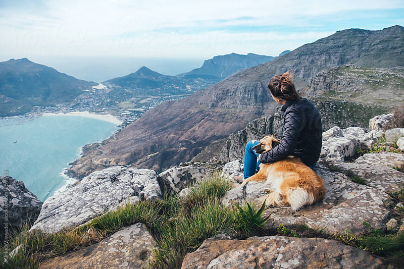 Hiker with pet dog on a mountain summit enjoying the view by Micky Wiswedel for Stocksy United